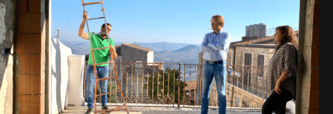 A Couple Standing On The Balcony of a 1 Euro House In Italy Talking To A Workman With A Ladder