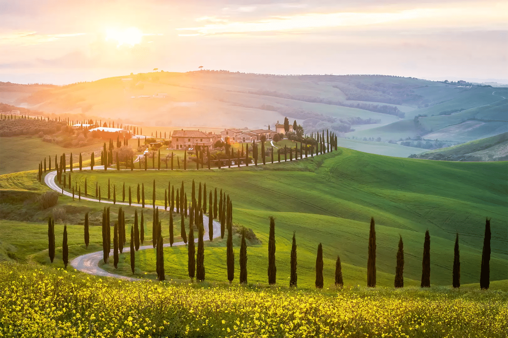 Conde Nast Traveller picture of Italian Countryside with fileds and trees lining a snaking road off to an estate in the distance behind which the sun is setting