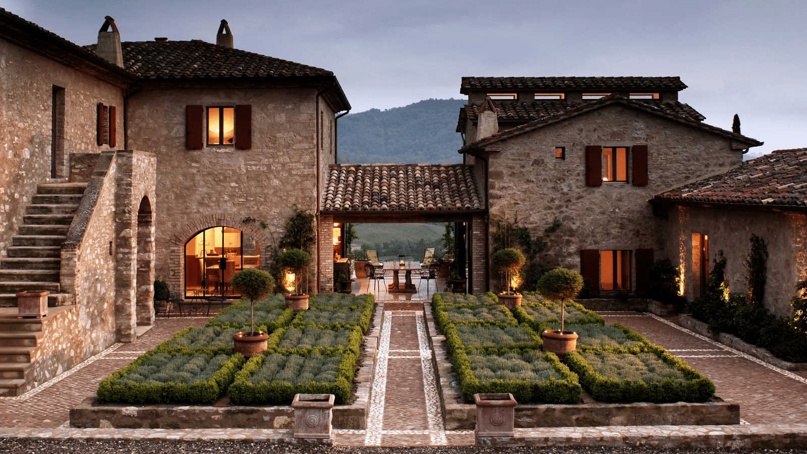 Courtyard of a house in Italy with two buildings linked by a tiled-roof portico with lights shining from the windows in the evening