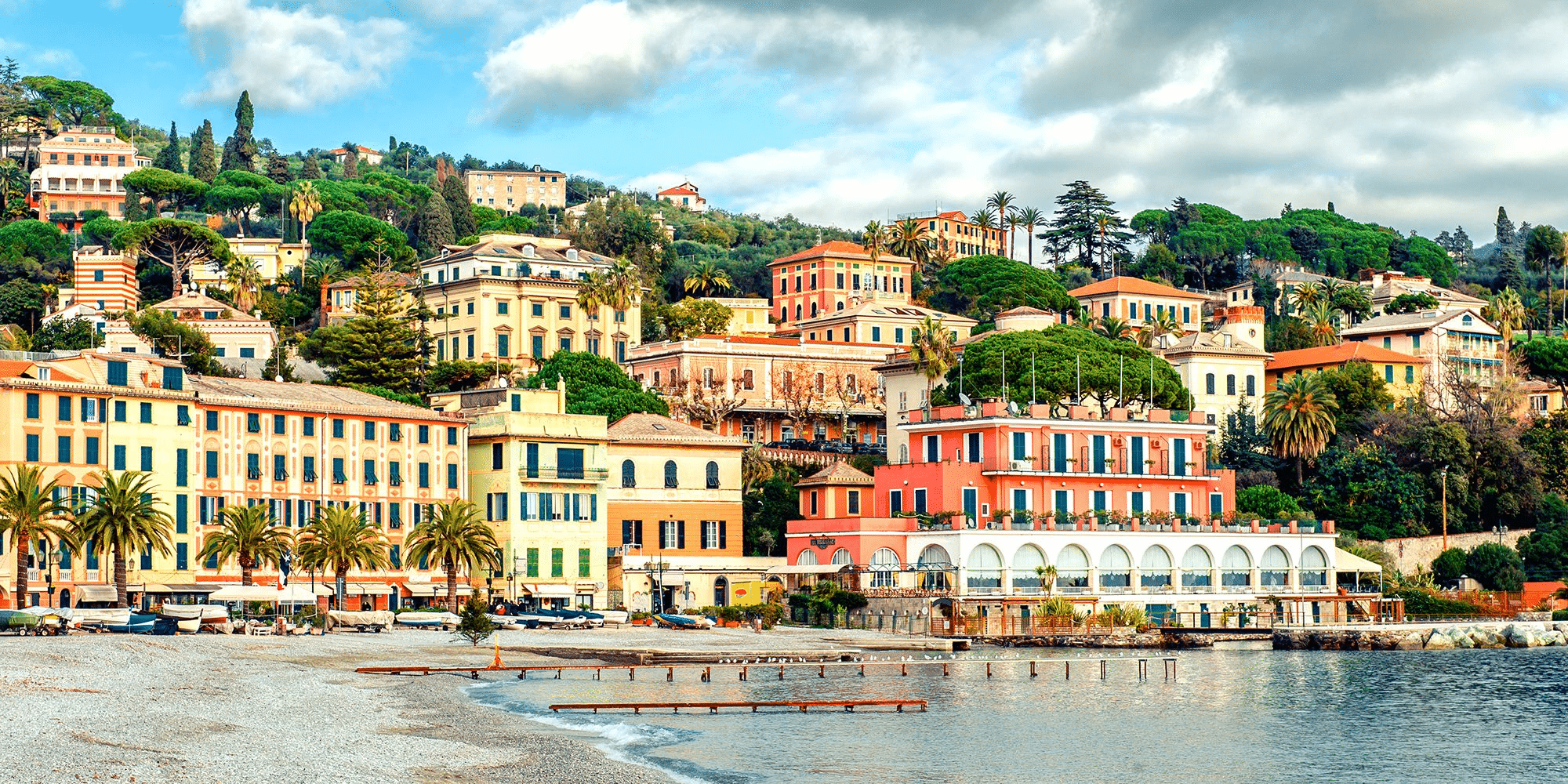 Image of an Italian town rising from the edge of a body of water up a slope with yellow-stone buildings