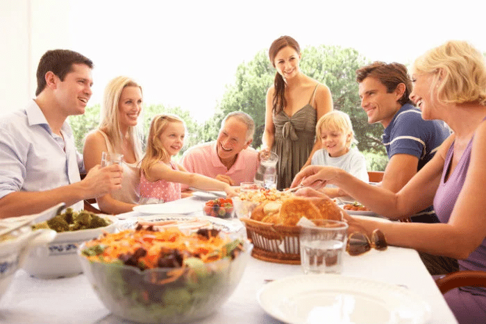 Image of multiple generations of a family sitting and talking and laughing at a table with bright sunshine and trees behind them