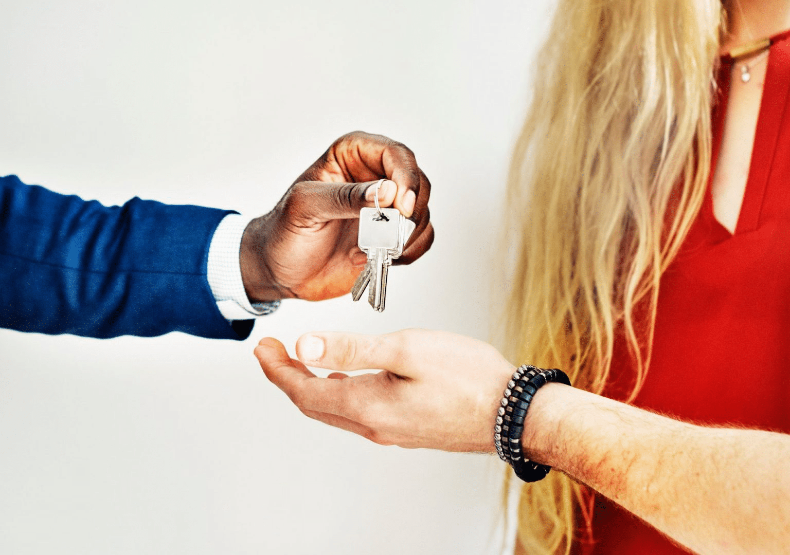 Picture of a black man wearing a shirt and jumper's hand handing over a set of keys with a white woman with blonde hair and a bracelet on