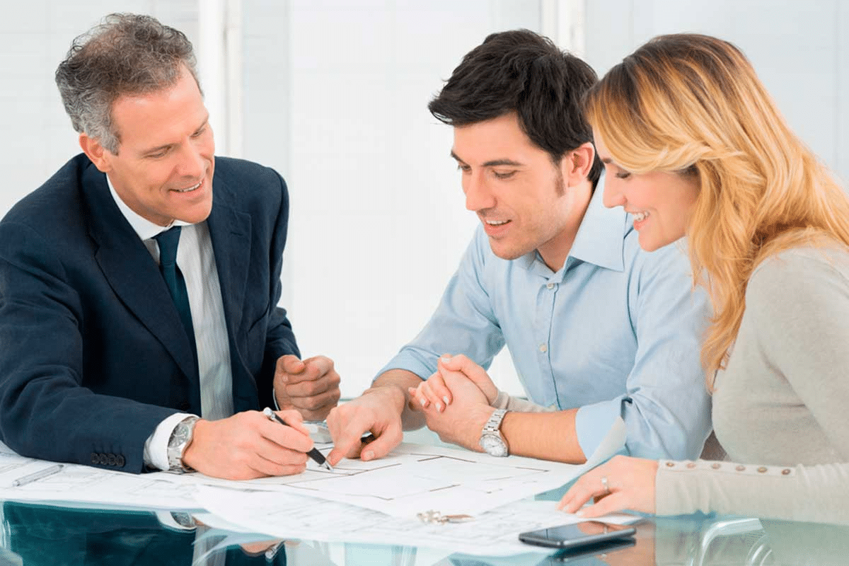 Picture of a couple talking to and smiling with a property agent wearing a suit