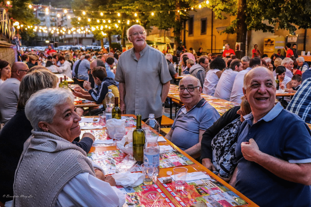 Picture of a laneway in the evening filled with tables full of food and drinks with elderly people sitting at them and looking off into the distance with strung fairylights behind them