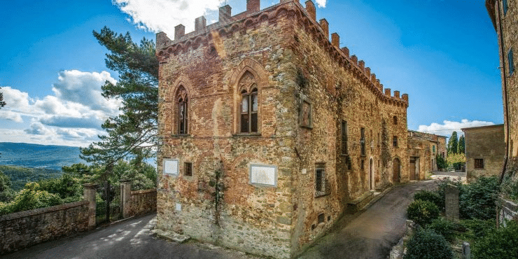 Picture of the corner building of a castle made from stone with bright sunshine and blue skies behind it backed only by a single tree and clouds