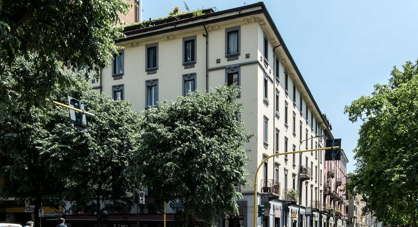 Picture of the upper corner of an apartment block in Milan, Italy, surrounded by trees and blue skies