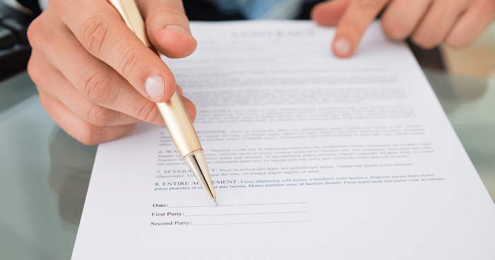 Someone holding a bronze-coloured pen in their right hand and signing a contract